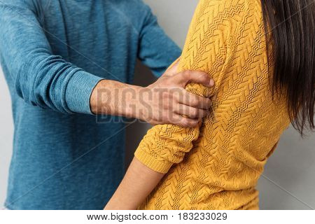 Cropped image of aggressive man holding woman strongly isolated