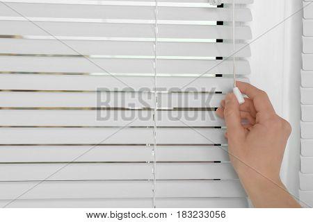 Female hand opening white jalousie on window, closeup
