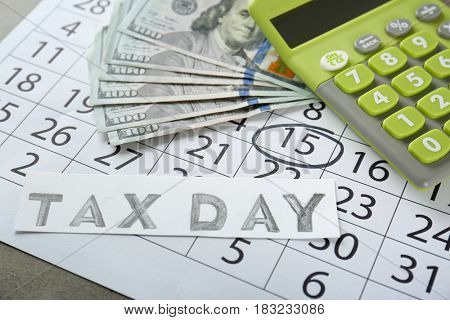 Green calculator and money on calendar. Tax concept