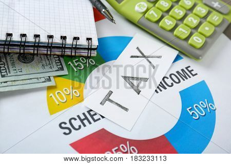 Tax concept. Schedule of income with money and office stationery, closeup