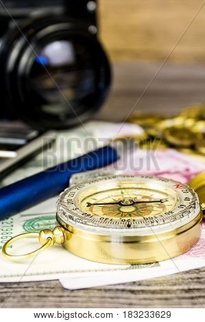 Composition of a tourist compass, banknotes, coins, calculator, pen and fotocamera on the gray wooden table