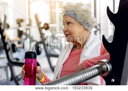Side view portrait of smiling female retiree drinking water during workout in gym. She keeping shaker in hand