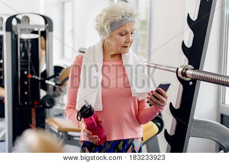 Serene female retiree looking at mobile while situating in gym. She keeping blender bottle in hand
