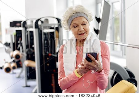 No matter how old you are, music and sport is always in fashion. Outgoing granny listening music and watching at cellphone in fitness center
