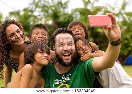 Brazilian tourists taking selfie photos with Brazilian Natives (Indios)