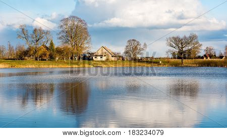 Reflections Of Coutry House In The Lake Water