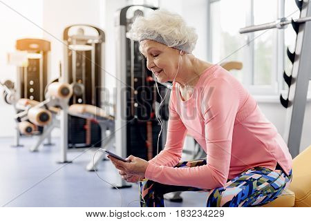 Side view female retiree demonstrating happiness. She listening music and looking at mobile in gym. Sport concept