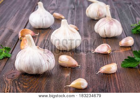 Top View, Flat Lay. Garlic Clove And Garlic Bulb On A Brown Wooden Table.