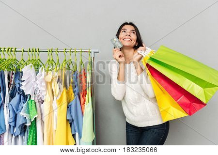 Picture of young cheerful woman standing over grey wall while holding shopping bags and talking by mobile phone. Looking aside.