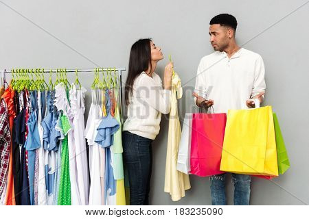 Picture of young lady begging clothes over grey wall from confused man holding shopping bags. Looking aside.