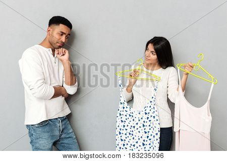 Young woman asking her boyfriend about choosing dresses isolated