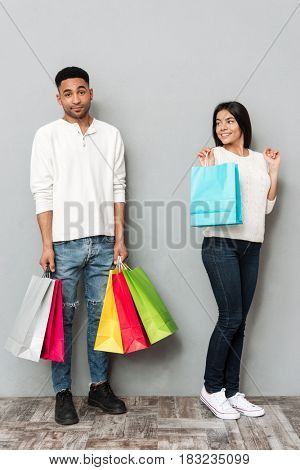 Image of young loving couple standing over grey wall and holding shopping bags.