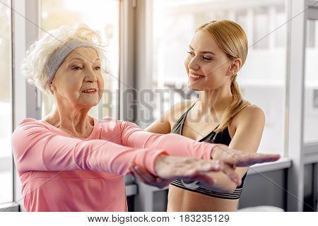 Keep your back straight. Smiling granny doing exercises with cheerful trainer in modern gym