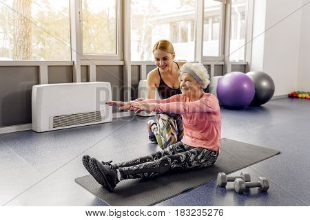Grandmother showing gladness while making exercises in gym. She sitting on mat. Beaming trainer locating near her