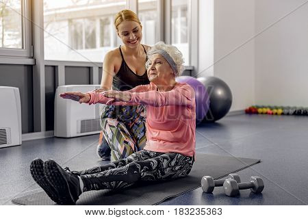 Cheerful young female coach asking how to do workout to smiling old woman in fitness center