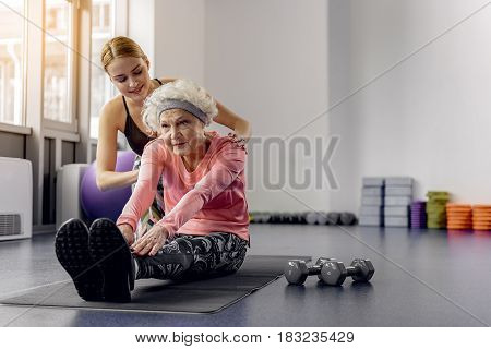 Happy girl helping making exercises to serious beneficiary. She sitting on mat. portrait