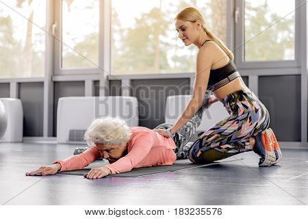 Grandmother expressing tranquility while making stretching in fitness center. Beaming young female helping her