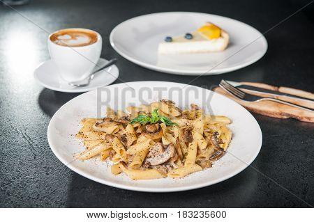 Vegeterian Tasty Dinner - Creamy Mushroom Penne Pasta, Cup Of Coffee And Fruit Cheesecake On Dark Ta