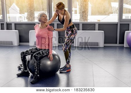 Full length outgoing retiree speaking with happy trainer in gym. She sitting on fitball