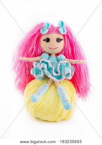 A knitted doll sits on a tangle of yarn. A doll with pink hair. Eyes of the button.