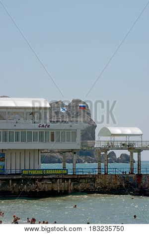 SUDAK, CRIMEA, RUSSIA - JUNE 27: Summer sun is illuminating two-story building of cafe with outdoor terrace on pier, swimming people bellow and Alchak cape behind it on June 27, 2015 in Sudak, Crimea, Russia.