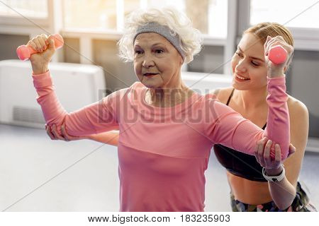 Pensive grandmother making exercises with dumbbells. Smiling woman helping her in gym. Portrait