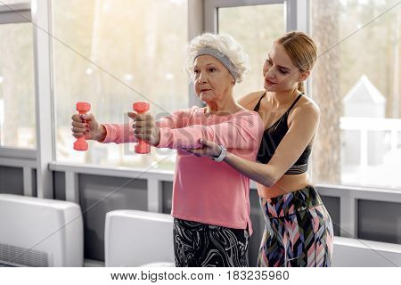 Calm female retiree increasing muscle strength in fitness center. Happy young coach training her in fitness center