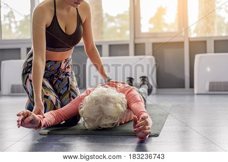 Calm female helping retiree making exercises in right way. She leaning on mat in gym