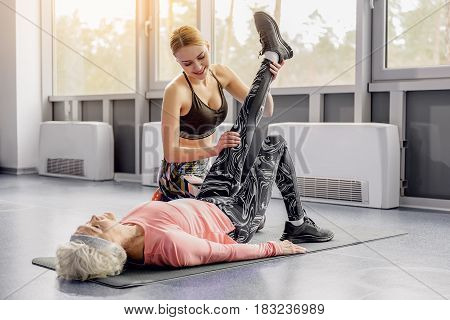 Young female expressing happiness while helping serene retiree making exercises in gym