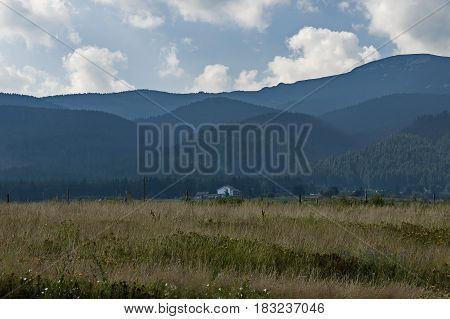 Majestic mountain top overgrown with coniferous forest, valley, glade and house, Rila mountain, Bulgaria
