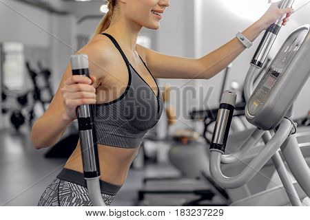 Lady demonstrating happiness while doing cardio on body-builder in fitness center