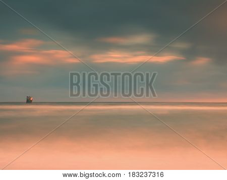 Sea Birds Sit On Boulder Sticking Out From Smooth Wavy Sea. Evening Wavy Ocean. Dark Horizon With Th