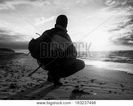 Man sit at evening sea. Hiker with backpack sit in squatting possition along beach. Vintage Style Toned effect