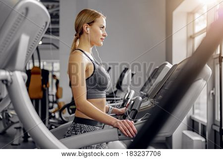 Side view serene female running on stepmill while listening music. She looking at window