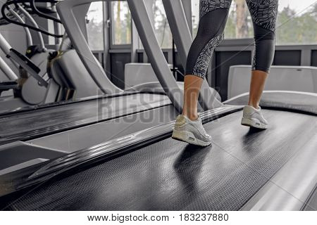 Close up of legs of woman wearing in sneakers. She running on treadmill