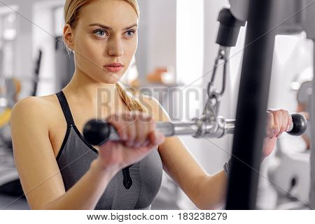 Serious young female making exercise on triceps with pulldown station in fitness center. Portrait