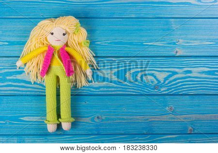 Knitted doll in bright clothes. A handmade toy. Doll on a blue wooden background. Copy space.