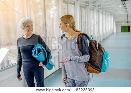 Outgoing grandmother speaking with happy woman indoor. They going from gym