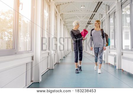 Outgoing grandmother speaking with beaming woman while going in corridor after workout in fitness center