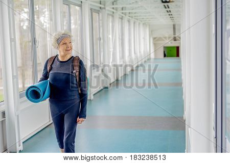 Female retiree expressing happiness while going in long hall after good training in modern gym. She looking at window. Copy space