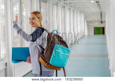 Lady expressing happiness while biding good-bye. She waving hand while going along corridor after fitness