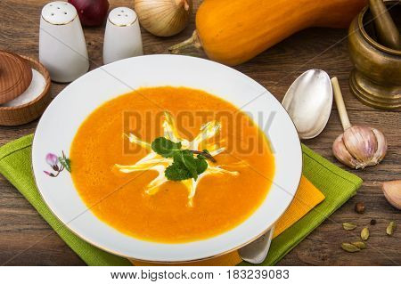 Spicy pumpkin puree soup on plate. Studio Photo