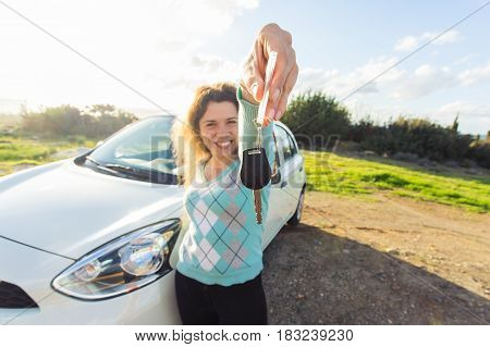 Happy woman driver showing car keys on the background of her automobile outdoors