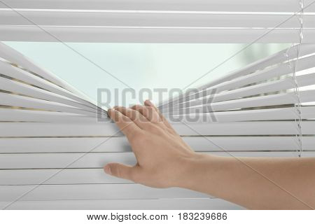 Female hand separating slats of blinds to see through window