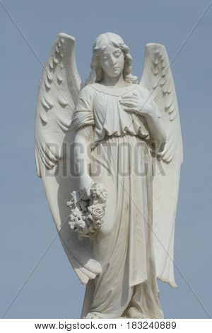 Gravestone memorial with angel holding wreath of flowers against overcast sky