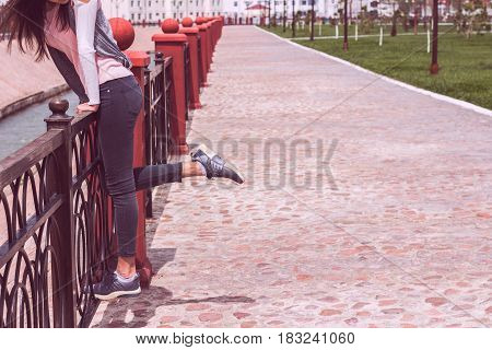 Young girl in jeans and sneakers sports shoes walking on road near metal fence. Leisure and lifestyle