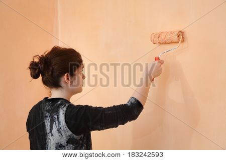 Young Worker Paint Wall In A Room To Orange