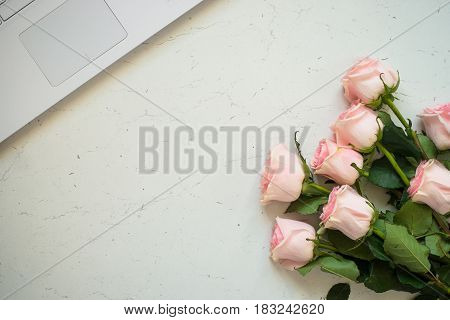 Notebook and bouquet of pink roses flower at white stone table. Top view copy space. Work and holiday