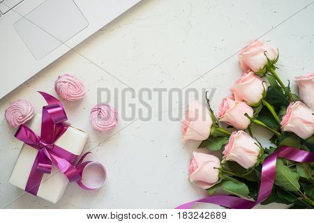 Pink rose notebook present and sweetness at white stone table. Top view copy space. Work and holiday