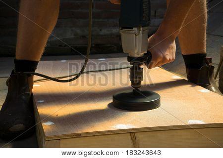 Man sawing hole for wood cornhole board DIY project